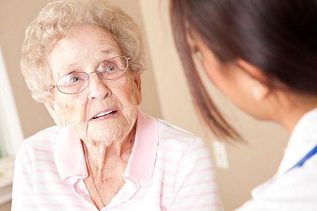 Elderly woman talking to nurse